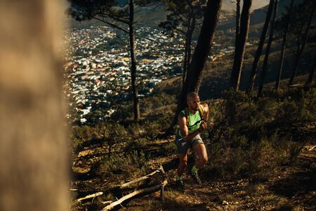 Fit sportsman sprinting over rocky trail on mountain. Man running uphill on mountain path.