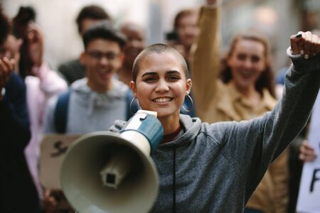 Young woman standing outdoors with group of demonstrator in background. Woman protesting with a megaphone outdoors on road.