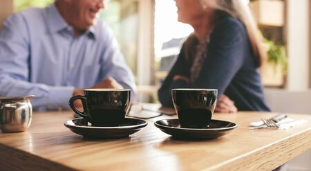 Two cups of coffee on table with senior couple sitting in background at a cafe. Fresh cup of coffee on cafe table with retired man and woman sitting at back.