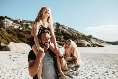 Family of three on a beach vacation. Father giving daughter ride on shoulders as they walk at the seashore with mother.