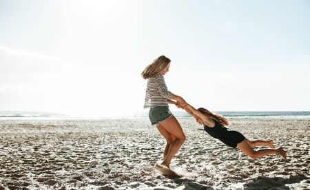 Mother and daughter having fun on the beach. Woman holding hands of the girl and spinning her on a beach