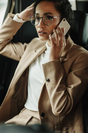 Businesswoman travelling to office in a car sitting on backseat and talking on cellphone. Businesswoman receiving a phone call on the backseat of a car.