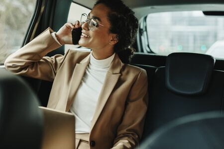 Cheerful woman in business suit sitting on backseat of her car and talking on mobile phone. Businesswoman using phone while traveling by a car.