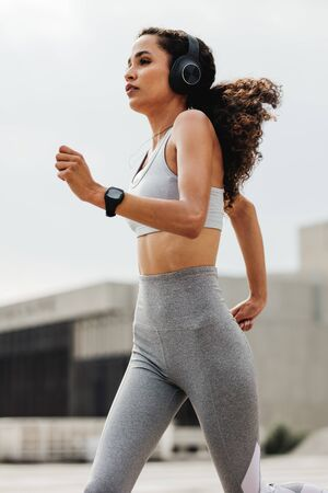 Athletic woman running through the city. Female in sports clothing and wearing headphones running outdoors in the city.
