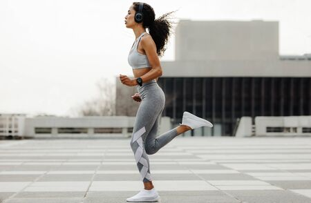 Full length shot of a fitness woman jogging in the city. Woman wearing sportswear and headphones running outdoors.