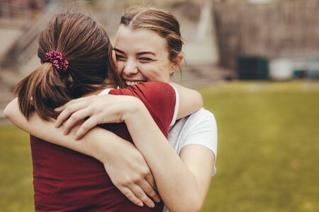 Two girls hugging each other in school campus. High school students smiling and embracing outdoors.