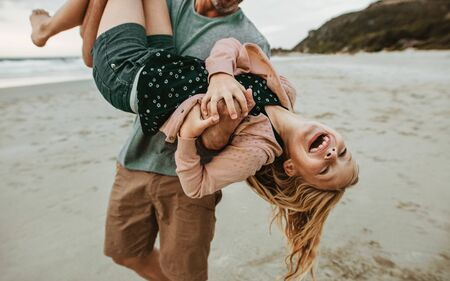 Man carrying his daughter and walking on the beach. Father and daughter having a great time on the beach vacation.