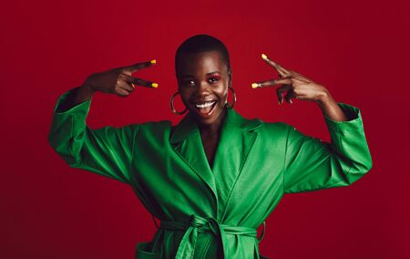 Excited woman with colorful makeup on red background. Attractive african woman in green dress looking at camera showing peace sign with both hands.