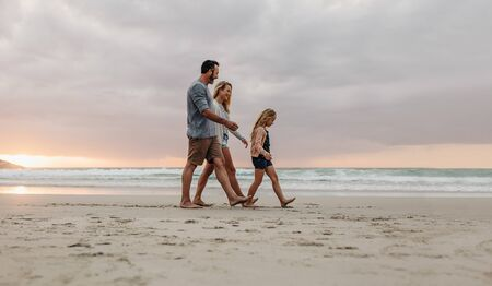 Family of three walking together on a beach vacation. Couple with their daughter on evening walk along the beach. 写真素材