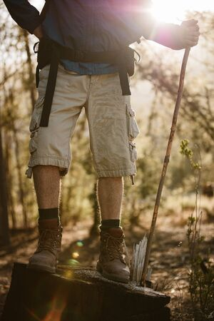 Low section shot of a male hiker standing no a rock holding a stick. Senior man hiking in nature, taking a break.