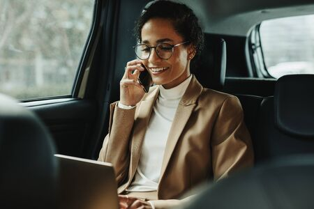Businesswoman working on laptop and talking on phone while travelling in a taxi. Woman sitting on back seat of car using laptop and phone. 스톡 콘텐츠 - 149638023
