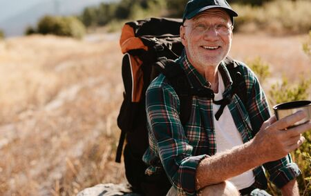 Senior male backpacker having coffee on hiking trail. Male hiker taking rest and drinking fresh coffee, looking at camera and smiling.