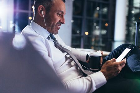 Businessman sitting at airport lounge, waiting for his flight. Mature male business professional wearing wireless earphones using mobile phone. 写真素材