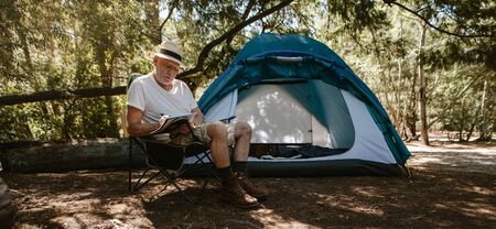 Mature man writing a book at campsite. Senior male traveller writing a book at camping site. He is sitting on a chair outside the tent. 写真素材