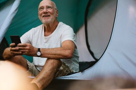 Smiling senior man sitting in tent with his mobile phone. Retired man camping in nature looking away and smiling.