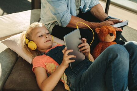 Girl using tablet pc with her father sitting on side with a mobile phone at airport waiting lounge. Family relaxing at airport waiting lounge. 스톡 콘텐츠 - 149638040