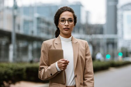 Portrait of a confident businesswoman standing outside with a digital tablet. Businesswoman with eyeglasses on city street staring at camera. 写真素材