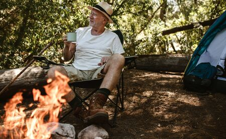 Retired man sitting near campfire and having coffee. Senior male camping in forest having a refreshing coffee in morning.