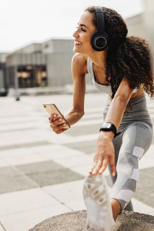 Woman exercising in the city. Female with headphones listening music from her phone.