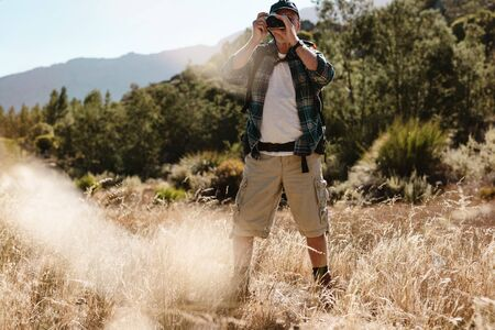Senior man on hiking trip taking photos with a digital camera. Male hiker photographing a nature.