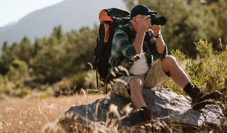 Senior man photographing with a digital camera. Retired man sitting on a rock and taking pictures on hiking trip. 写真素材