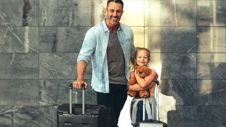 Father and daughter standing together with their luggage at airport. Family of two travelling together, looking at camera and smiling. Man with a travel bag and girl holding teddybear.