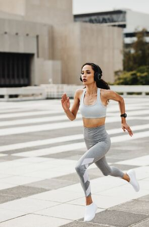 Sportswoman sprinting in the city. Woman in sportswear and headphones fast running outdoors. 写真素材