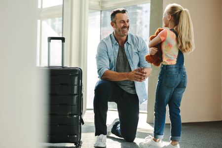 Daughter holding a teddybear greets her father at the entrance door when he arrives back from a business trip. Daughter talking with her father just arrived from a tour with a travel case. 写真素材