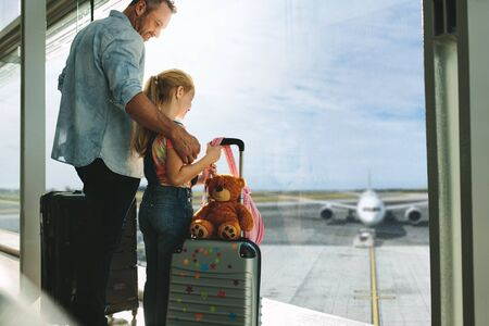 Father and daughter looking at planes while waiting in the airport. Man with his daughter standing by a large window at airport terminal.
