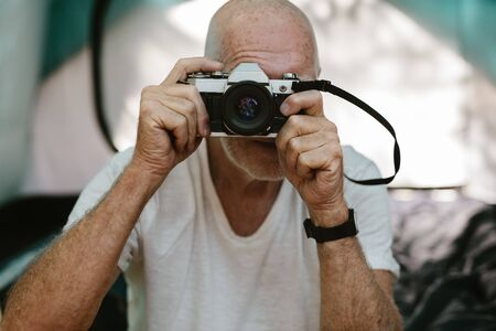Closeup of a senior man sitting outside his camping tent and photographing with a digital camera. Retired man taking some snaps while camping in nature.