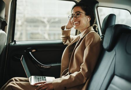 Smiling businesswoman travelling in a taxi with laptop. Woman with laptop sitting in back seat of her car looking away and smiling.