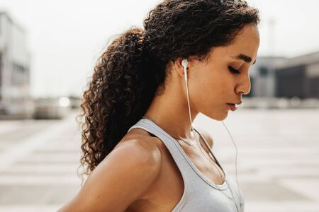 Sportswoman standing outdoors with earphones. Female athlete taking a break after intense training session.