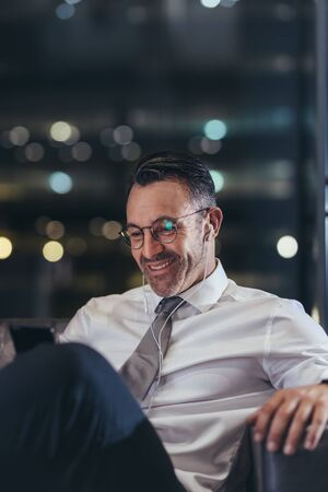 Businessman waiting at the airport looking his phone and smiling. Man in formalwear sitting at airport using his smart phone.