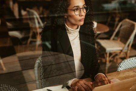Businesswoman at coffee shop working on laptop and looking away thinking. Female business professional working from a cafe.