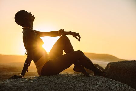 Silhouette of a woman sitting at the beach with sun shining from behind. Female in bikini relaxing at the beach in evening.