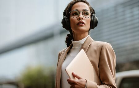 Businesswoman wearing headphones walking down the city street holding a laptop. Businesswoman wearing headphones and laptop in hand on city street.