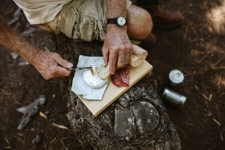 POV shot of a senior man eating at campsite. Man on camping sitting on a log and having food.