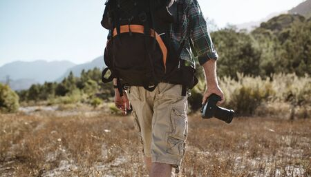 Rear view of a senior man carrying a backpack hiking in nature holding a digital camera. Man on hiking trip.