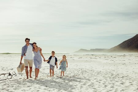 Couple with their children walking to the picnic spot on beach. Family going on picnic at beach. 写真素材