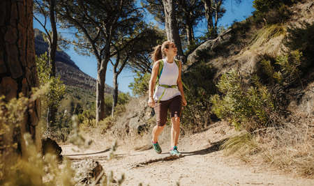 Woman walking on a mountain trail. Female on hiking trip looking up at the mountain.