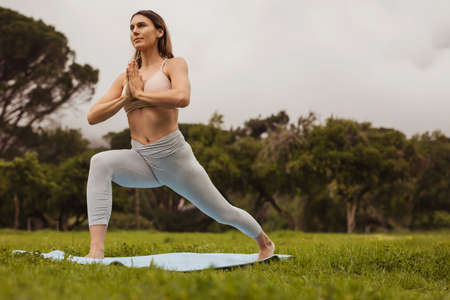 Fitness woman practising yoga in a park. Portrait of a woman doing forward lunges while practising yoga outdoors.