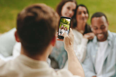 Close-up of a man using mobile phone for photographing friends at the picnic. Focus on cell phone display.