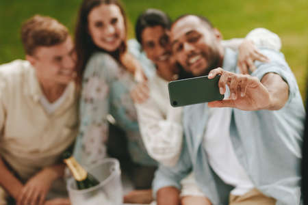 Friends taking self portrait with a cell phone at the park. Group of young people on picnic taking a selfie.