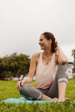 Portrait of a smiling woman sitting in park on a fitness mat. Cheerful female sitting in the meadows enjoying nature after her workout.
