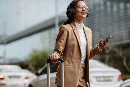 Female in businesswear ordering taxi online with her luggage while standing on a street. Smiling woman traveller with headphones standing on street with luggage bag listening to music on mobile phone.