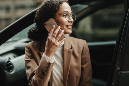 Businesswoman sitting in her car and talking on phone. Woman in businesswear making a phone call while sitting in her car.