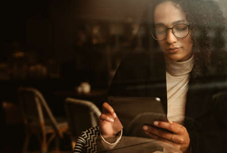 Businesswoman sitting at a cafe using digital tablet. Woman in a coffee shop with reading something in her digital tablet.