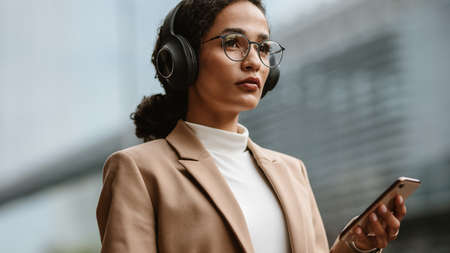 Confident female executive listening to music on cell phone. Businesswoman wearing headphones and holding a phone while standing outdoors on city street. Banque d'images