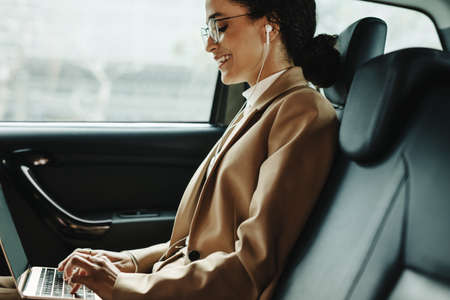 Side view of a smiling businesswoman working on laptop while travelling in a taxi. Woman using laptop in back seat of car. Banque d'images