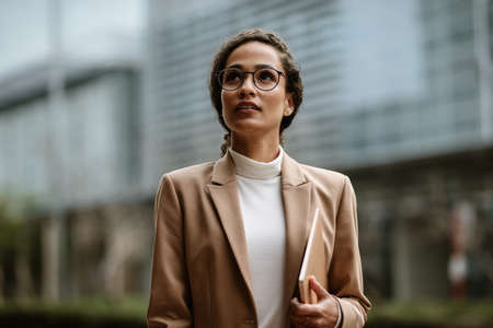 Businesswoman holding a laptop walking outdoors. Woman in formalwear and eyeglasses walking in the city.